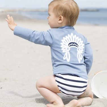 Petit Crabe boy in petrol blue Casey Chief turtleneck rash guard and striped swim nappy. UV sun protective swimwear.