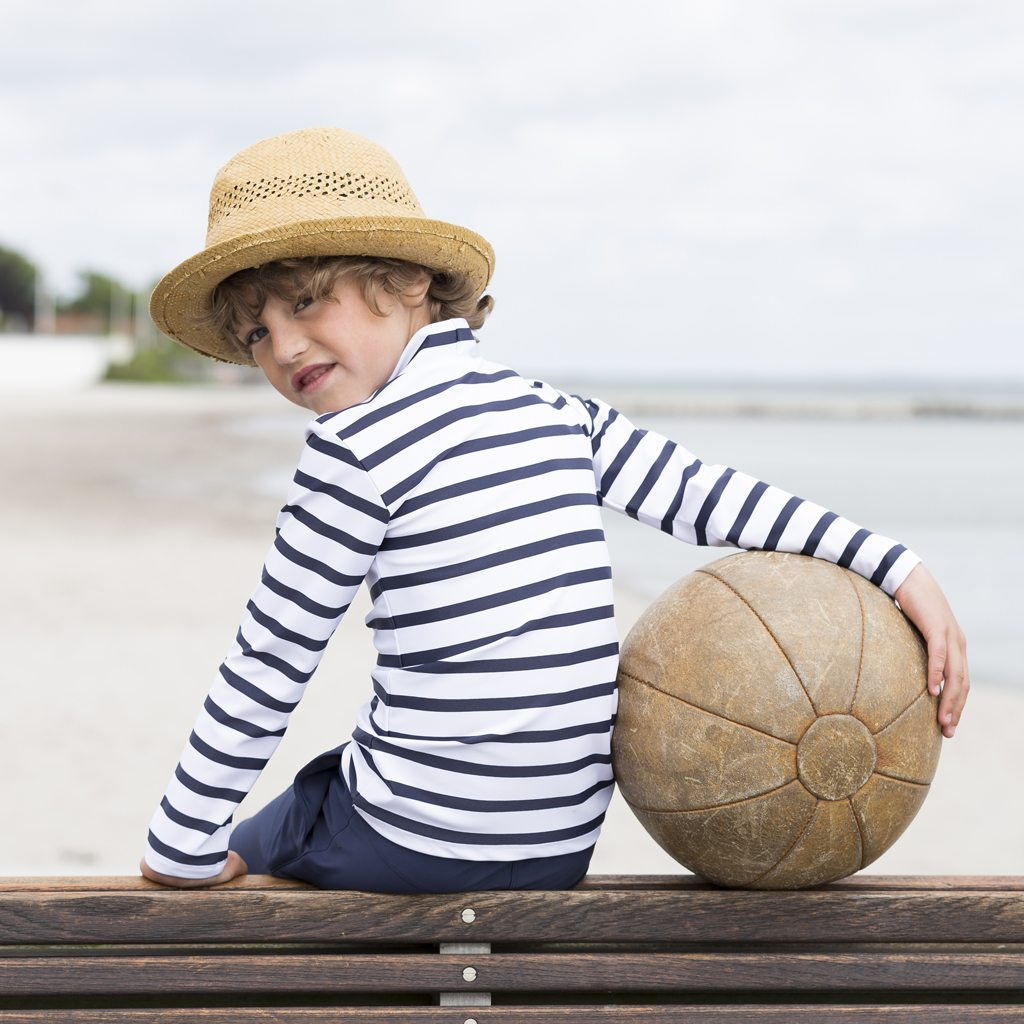 Petit Crabe boy in white and blue striped Casey turtleneck rash guard and bermuda shorts. UV swimwear for kids.