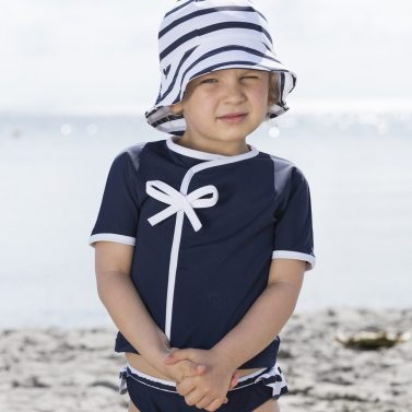 Petit Crabe girl in blue Julie Kimono with cute bow and Frey sun hat, sun protective clothing.