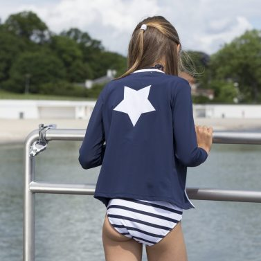 Petit Crabe girl with blue Etoile Zipper swim shirt with star application on the back. UV sun protective swimwear for kids.