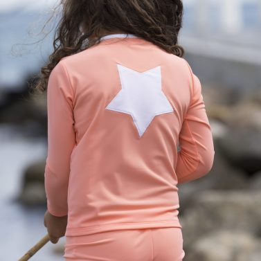 Petit Crabe girl with coral Etoile Zipper swim shirt with star application on the back. UV sun protective swimwear for kids.