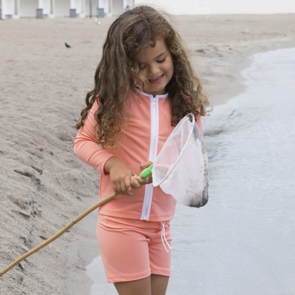 Petit Crabe girl with coral Etoile Zipper swim shirt with slong sleeves and zipper. UV sun protective swimwear for kids.