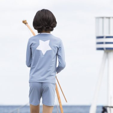 Petit Crabe boy with petrol blue Etoile Zipper swim shirt with star application on the back. UV sun protective swimwear for kids.