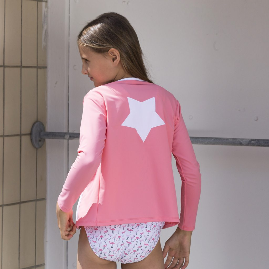 Petit Crabe girl with watermelon Etoile Zipper swim shirt and flamingo bikini bottoms. UV sun protective swimwear for kids.