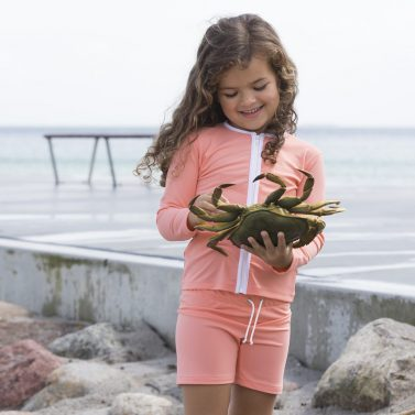 Petit Crabe girl in coral Alex swim trunks and rash guard with zipper. UV sun protective swimwear for kids.