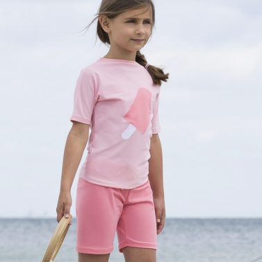 Petit Crabe girl in pink Alex swimshorts and Ice Cream applique rash guard. UV sun protective swimwear for kids.