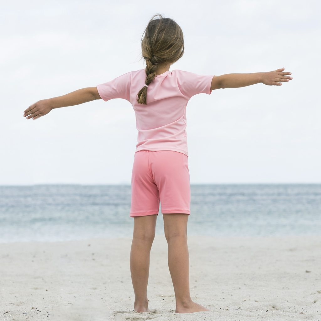 Petit Crabe girl in watermelon pink Alex swimshorts and rash guard. UV sun protective swimwear for kids.
