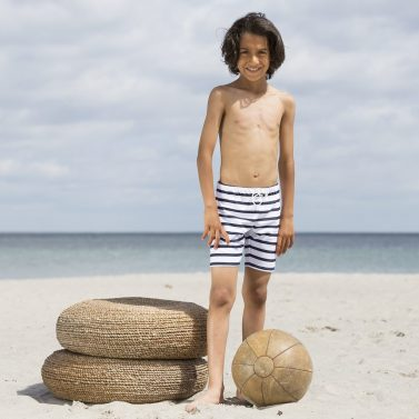 Petit Crabe boy in Alex white and blue striped swim trunks. UV sun protective swimwear for kids.