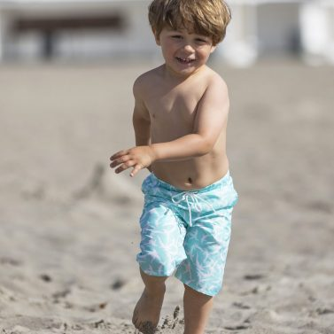 Petit Crabe boy running in mint dolphin board shorts. UV sun protective swimwear for children.
