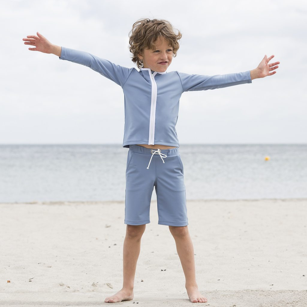 Petit Crabe boy in petrol blue long swim trunks and long sleeve rash guard. UV sun-protective swimwear for kids.