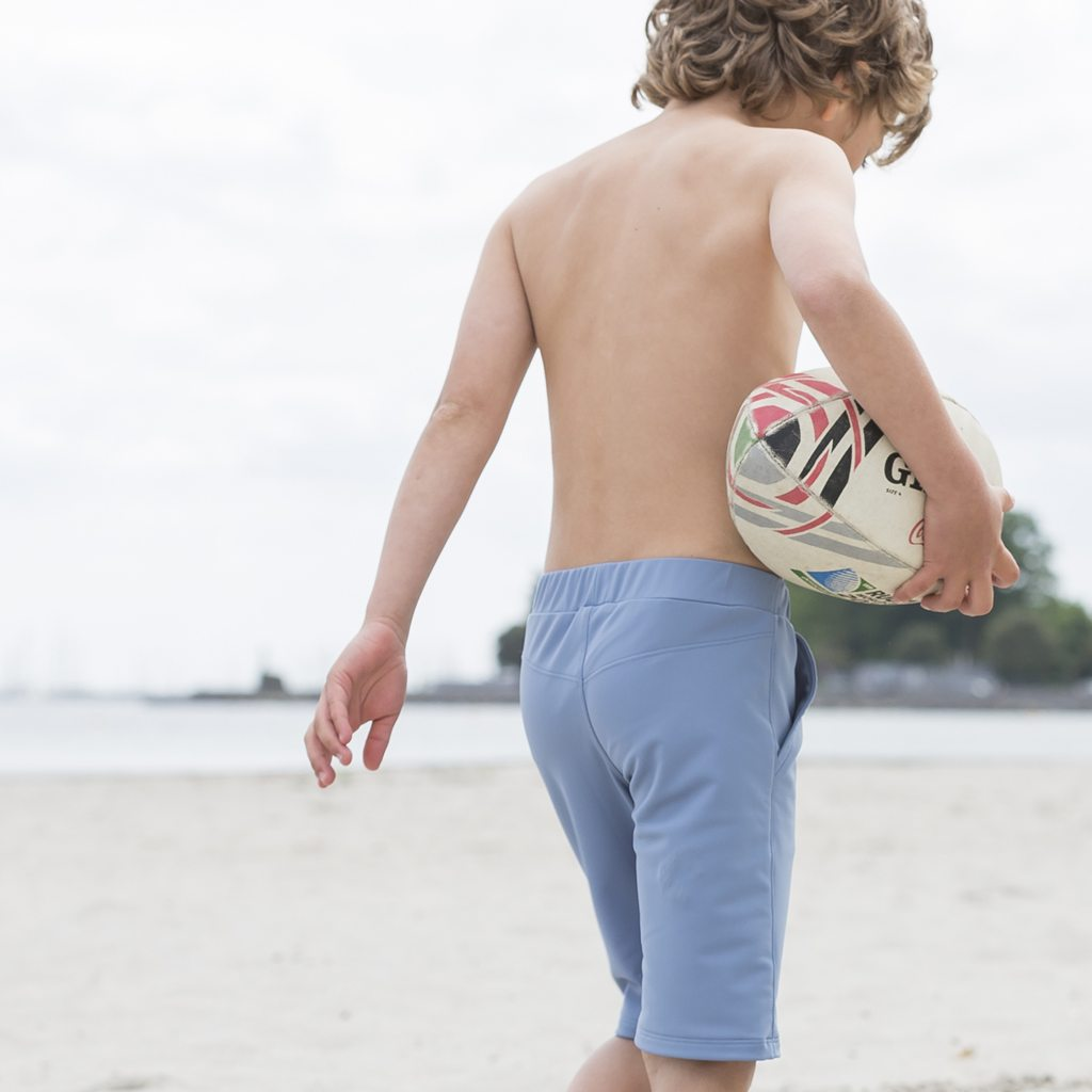 Petit Crabe boy in petrol blue long swim shorts. UV sun protective swimwear for children.