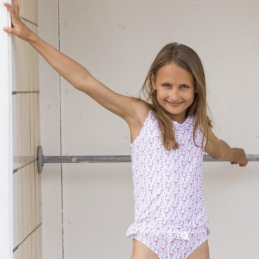 Petit Crabe girl in Flamingo Olivia Tankini and Zoe bikini bottoms with bow and ruffles. UV sun protective swimwear.