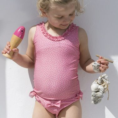 Petit Crabe girl in pink flower Olivia tankini and Zoe bikini bottoms with a bow, sun protective swimwear.