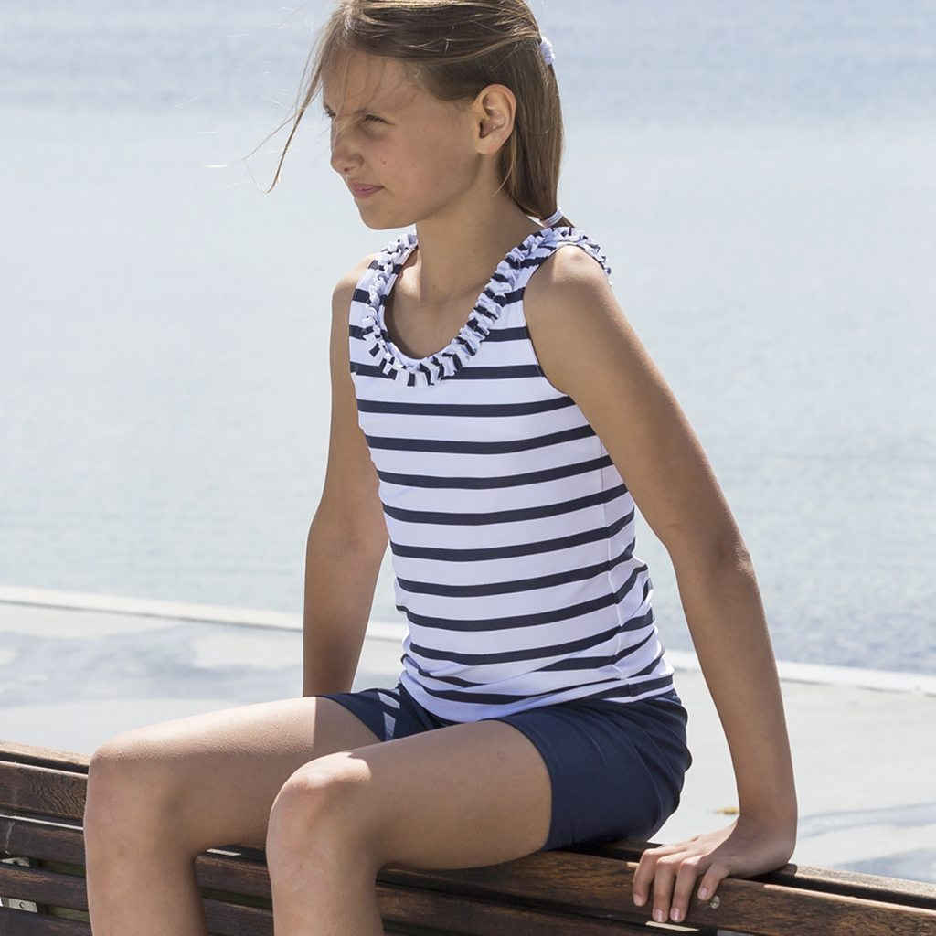 Petit Crabe girl in white and blue Olivia Tankini with ruffles and Alex swim trunks, sun protective swimwear.