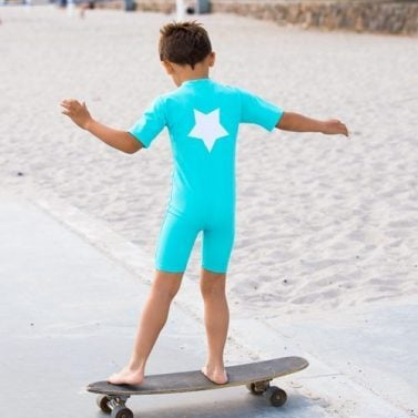 Petit Crabe skaterboy in turquoise Noe sunsuit with star application. UV sun-protective swimwear for kids.