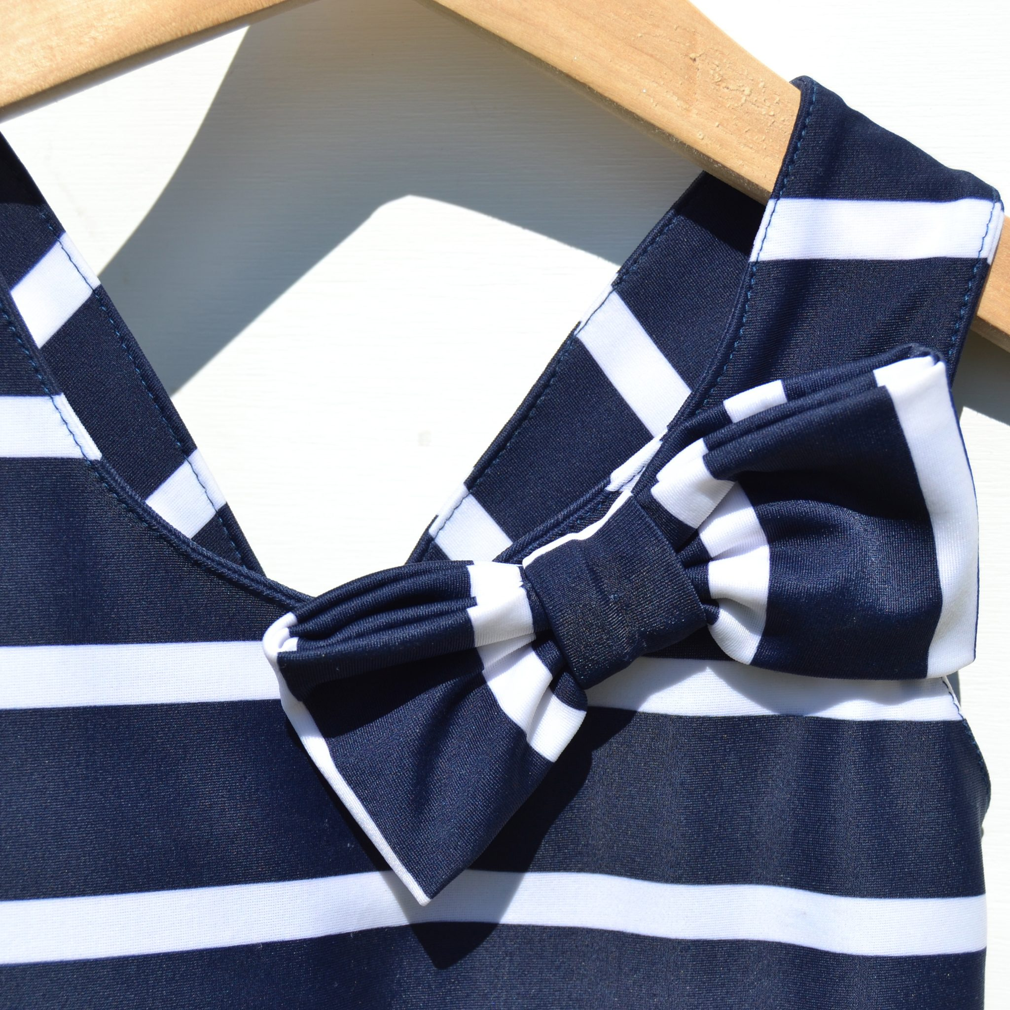 Petit Crabe cute bow detail on Elise Swimsuit for girls, sun protective swimwear for kids.