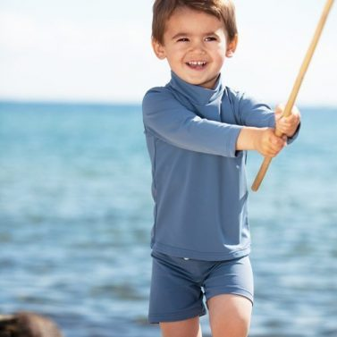 Petit Crabe boy in Casey STAR Turtleneck swim shirt and Alex swim trunks in grey.