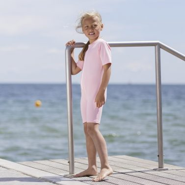 Petit Crabe Girl in Noe STAR UV sunsuit in soft rose and with zipper. UV sun-protective swimwear for kids.