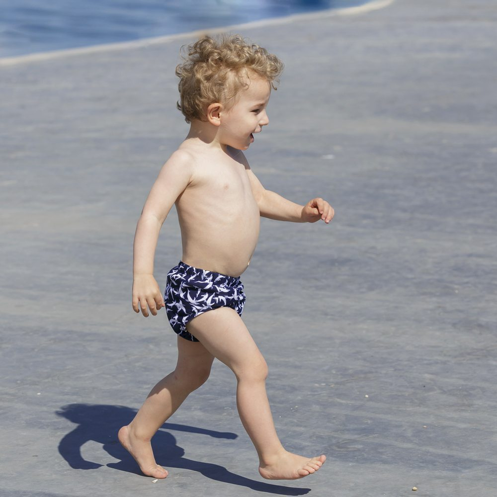 Petit Crabe baby boy in dark blue dolphin Leo swim nappies, sun protective beachwear for kids.