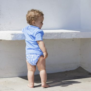 Petit Crabe baby boy in light blue sky dolphin Leo swim nappies and sun protective rash guard.