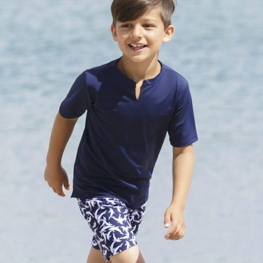 Petit Crabe boy in blue Hugo Star swimshirt and Mads Board shorts, uv sun protective swimwear for kids.