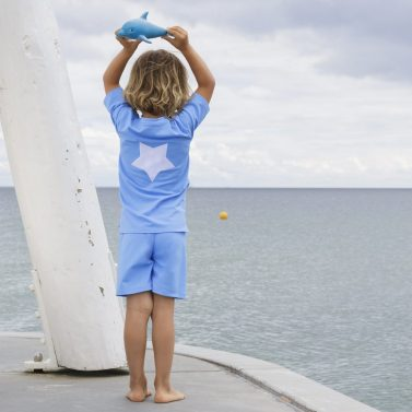 Petit Crabe boy in sky blue Hugo rash guard with star application on the back. UV sun protective swimwear for kids.