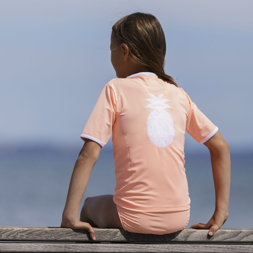 Petit Crabe girl in peach Salo rash guard with pineapple application. UV sun protective swimwear for kids.