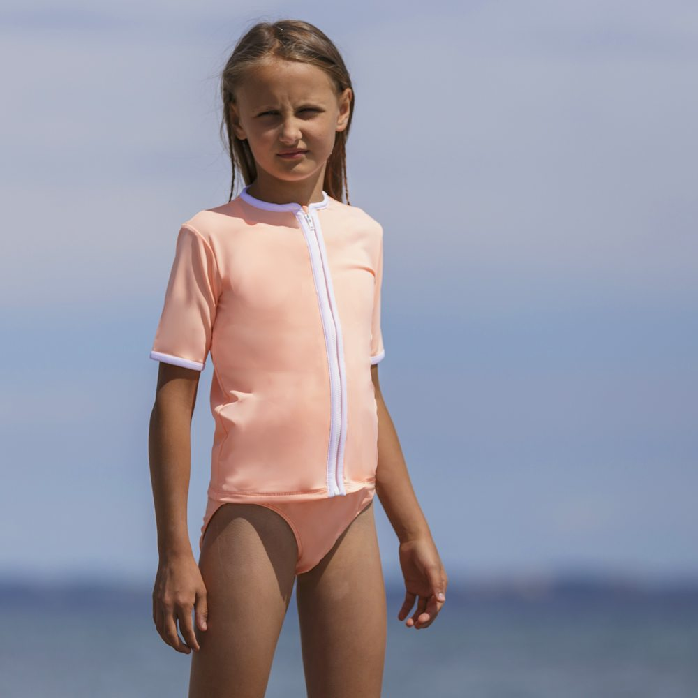 Petit Crabe girl in peach Salo rash guard with zipper and bikini bottoms. UV sun protective swimwear for kids.