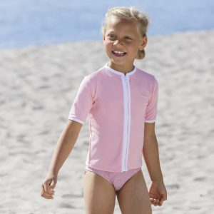 Petit Crabe girl in soft rose Salo rash guard with zipper, and bikini bottoms. UV sun protective swimwear for kids.