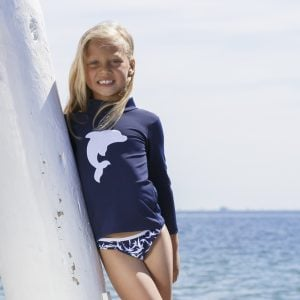 Petit Crabe girl in blue sun protective Casey turtleneck rash guard and bikini bottoms with dolphin print.