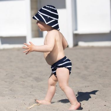 Petit Crabe baby boy in Blue White striped Leo Swim Nappy and Frey Sun Hat, sun protective swimwear for kids.