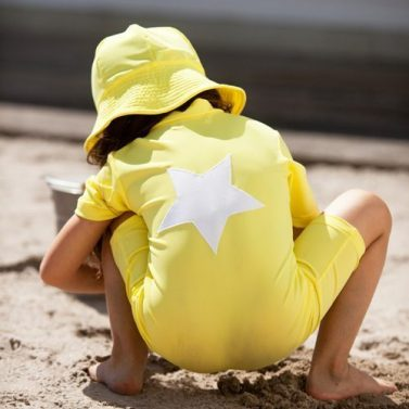 Petit Crabe child in yellow Noe Star sunsuit and Frey sunhat, uv sun protective wear for kids.