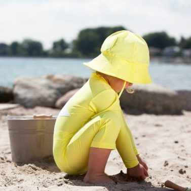 Petit Crabe girl in yellow Frey sun hat and Lou STAR sunsuit, sun protective swimwear.