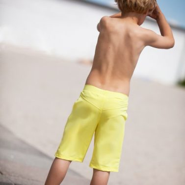 Petit Crabe kid in yellow long bermuda shorts, sun protective swimwear.