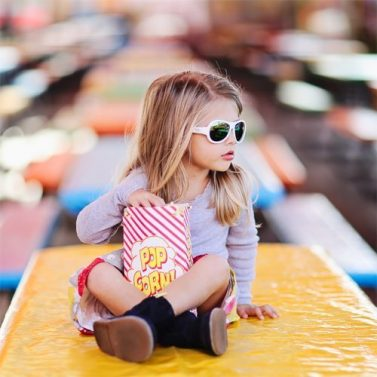 Petit Crabe sun protective wear, cool girl in white Babiator sunglasses eating popcorn