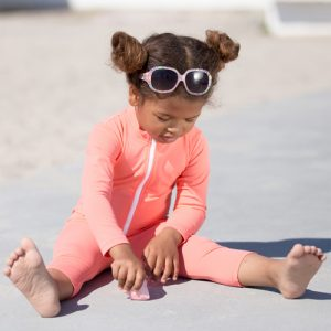 Petit Crabe Girl in Flamingo Lou PALM sunsuit with long sleeves and sunglasses, uv sun protective swimwear