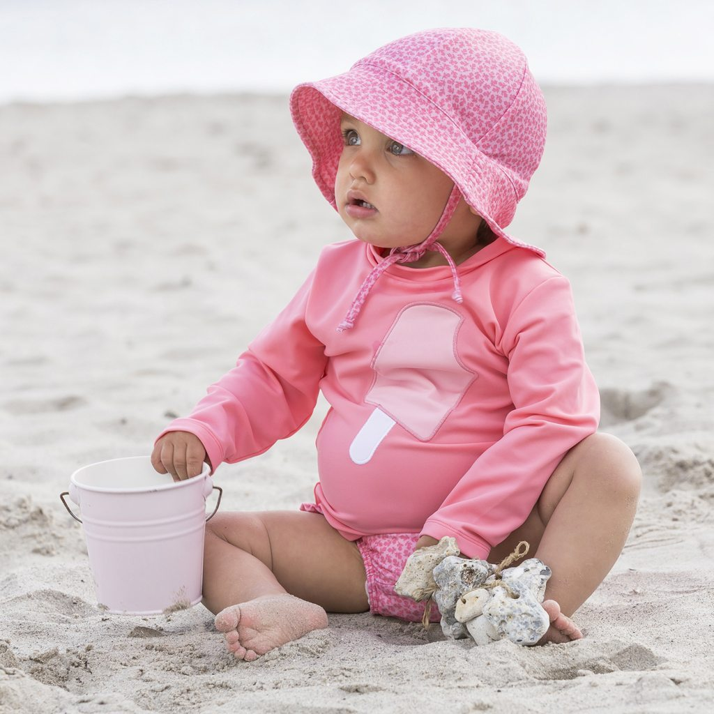 Petit Crabe baby girl in sun protective clothing, rash guards, uv sunhats and swim nappies