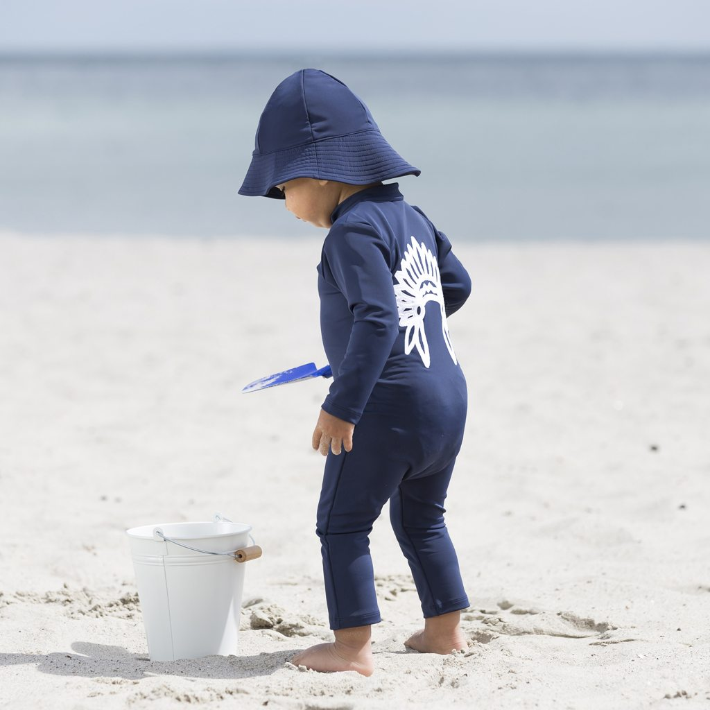 Petit Crabe baby boy in blue sun protective clothing, Lou Chief sunsuit with long sleeves and uv sunhat