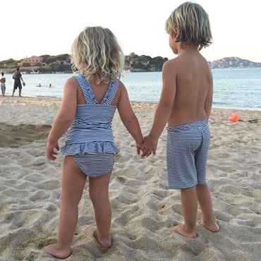 Petit Crabe kids in sun protective striped Olivia tankini, Zoe bikini bottoms and Alex boy swim trunks